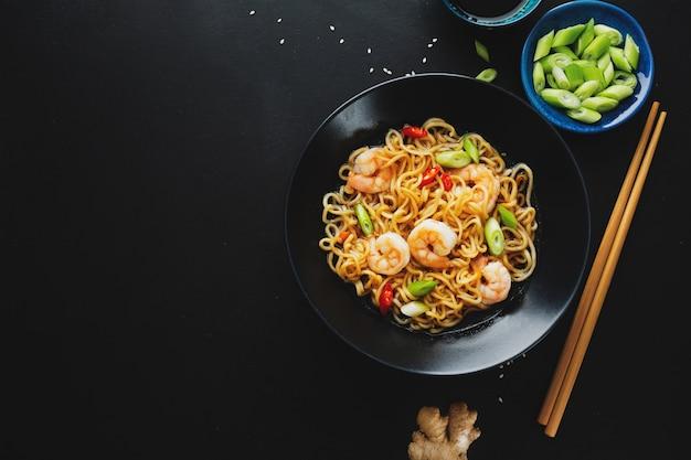 Smaczny, apetyczny makaron azjatycki z warzywami i krewetkami na talerzu na ciemnej powierzchni