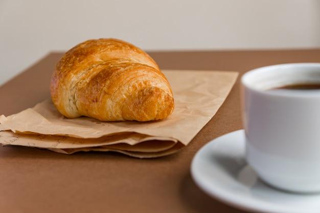 Smaczny breackfast. francuski rogalik podawany na papierze rzemieślniczym i filiżance czarnej kawy lub espresso na brązowym