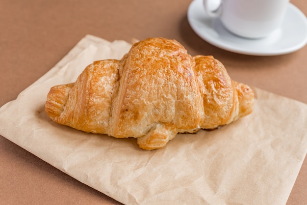 Smaczny breackfast. francuski rogalik serwowany na białym talerzu i filiżance czarnej kawy lub espresso na brązowym tle. skopiuj miejsce