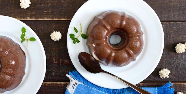 Smaczny budyń czekoladowy na białych talerzach na ciemnej powierzchni drewnianej. lekki niskokaloryczny deser na śniadanie. widok z góry, leżał płasko.