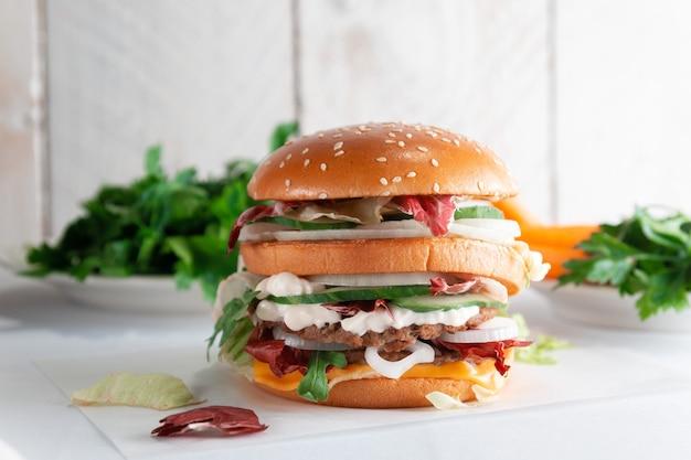 Smaczny burger na jasnym drewnianym stole