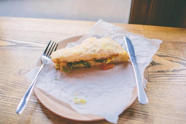 Smaczny burger na talerzu z widelcem i nożem. stań na drewnianym stole w kawiarni lub restauracji.