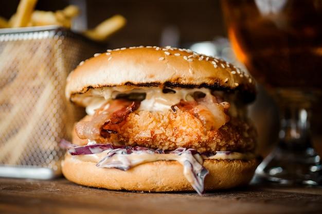 Smaczny burger z kotletem, serem i warzywami podany na drewnianym stole