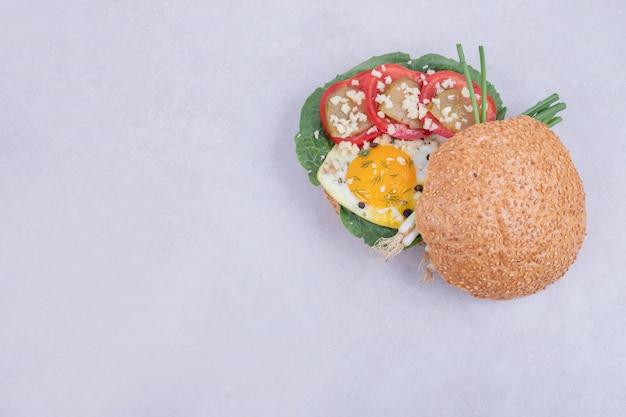 Smaczny burger z pomidorami, serem, sałatą na białym tle.