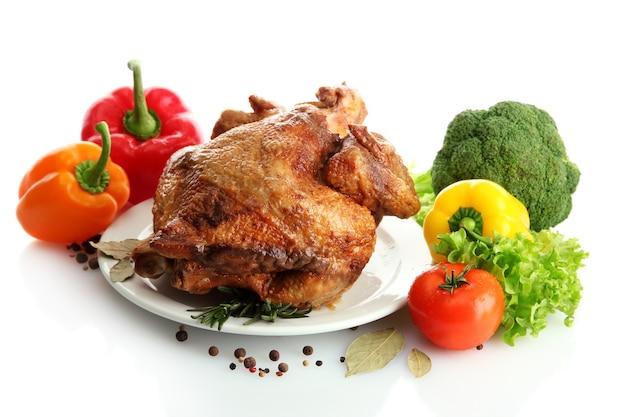 Smaczny cały kurczak pieczony na talerzu z warzywami, na białym tle