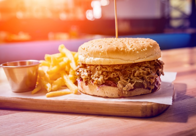 Smaczny cheeseburger i frytki na drewnianym stole. restauracja.