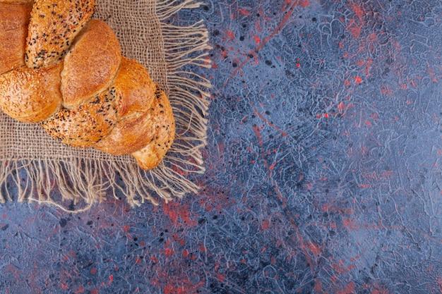 Smaczny chleb bagietkowy na ściereczce, na niebiesko.