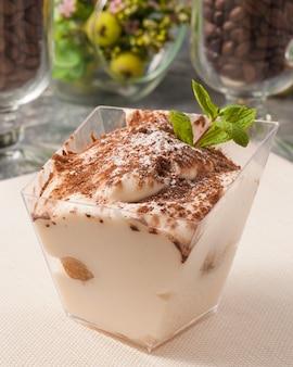 Smaczny deser tiramisu w prostokątnym pojemniku ozdobionym miętą
