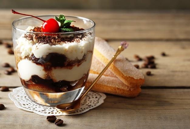 Smaczny deser tiramisu w szkle, na drewnie