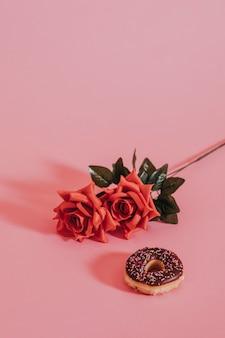 Smaczny glazurowany pączek obok róży