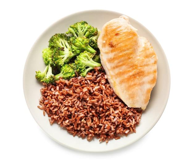 Smaczny gotowany czerwony ryż z mięsem i brokułami na talerzu, na białym tle na białej powierzchni