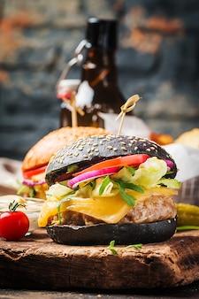 Smaczny grillowany klasyczny czarny burger wołowy z sałatą i sosem majonezowym na rustykalnym drewnianym stole, z miejscem na kopię