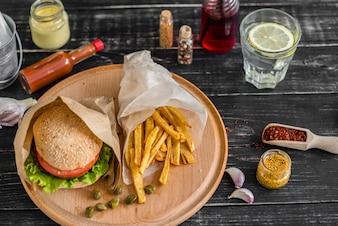 Smaczny hamburger z mięsem i warzywami na ciemnym tle. Fast food. Może być używany jako tło