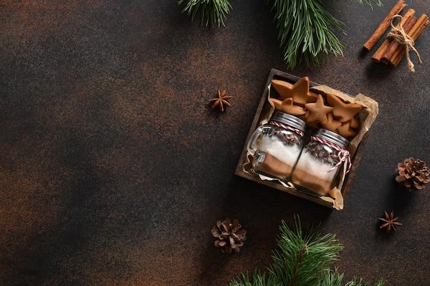Smaczny jadalny prezent świąteczny do robienia napojów czekoladowych i domowych ciasteczek na brązowym tle. miejsce na tekst. widok z góry.