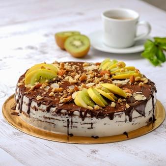 Smaczny kawałek ciasta czekoladowego z owocami, czekoladą, jabłkiem, kiwi na filiżance kawy americano