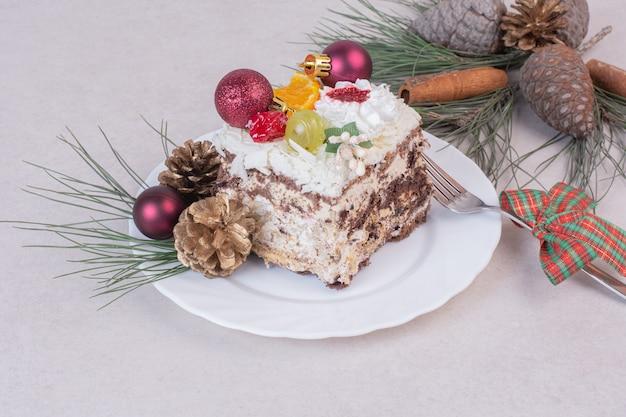 Smaczny kawałek ciasta z szyszkami i gałęzią drzewa