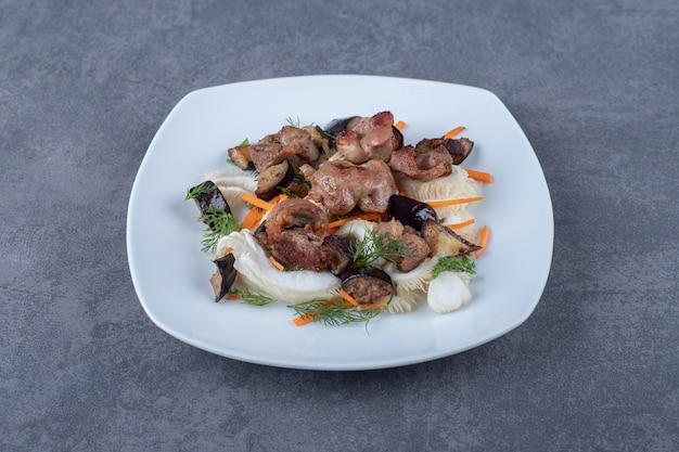 Smaczny kebab z grilla na białym talerzu.