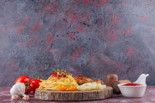 Smaczny, kolorowy, apetyczny gotowany włoski makaron spaghetti z sosem pomidorowym i świeżym czosnkiem.