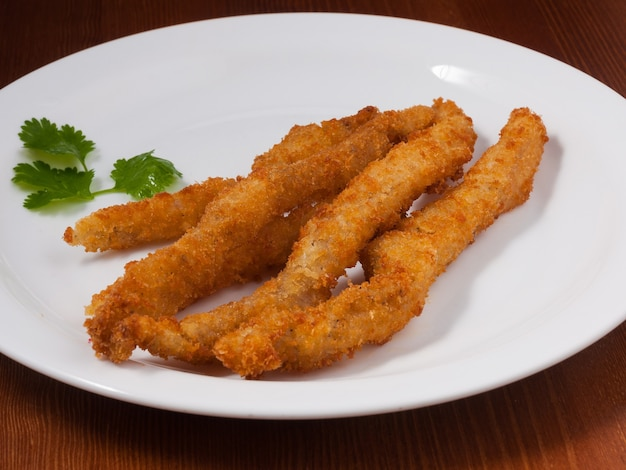 Smaczny kurczak pałeczkami w cieście na białym talerzu