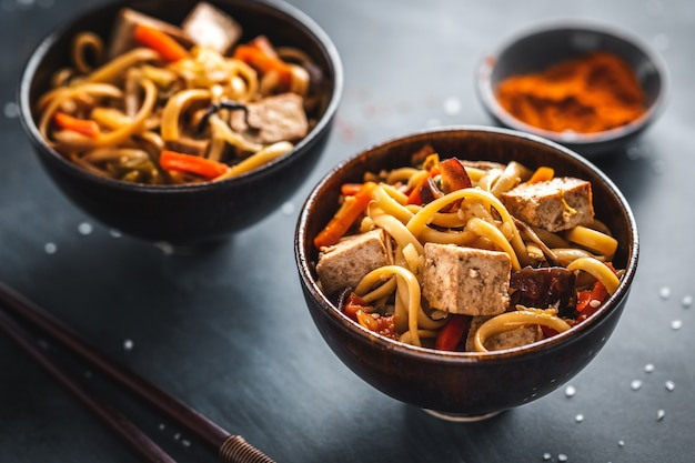 Smaczny makaron azjatycki z tofu z serem i warzywami na talerzach.