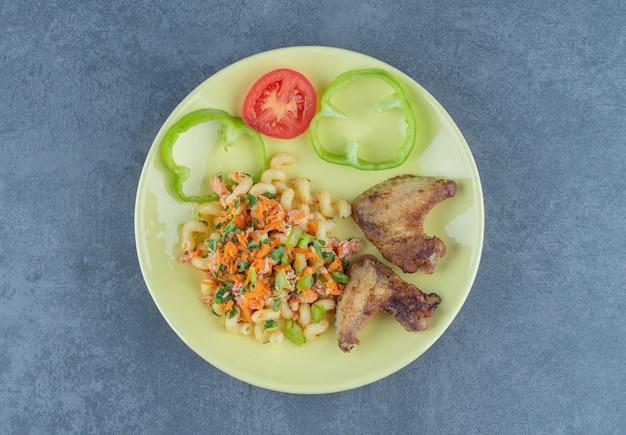 Smaczny makaron i skrzydełka z kurczaka na żółtym talerzu.