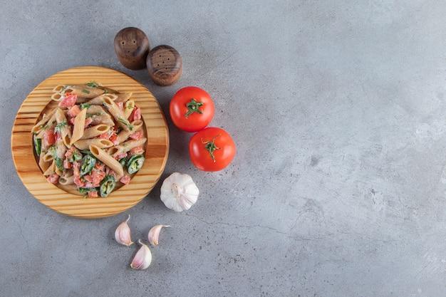 Smaczny makaron penne ze świeżymi posiekanymi warzywami na drewnianym talerzu.