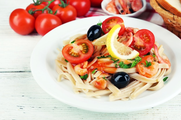 Smaczny makaron z krewetkami, czarnymi oliwkami i sosem pomidorowym na talerzu na drewnianym tle