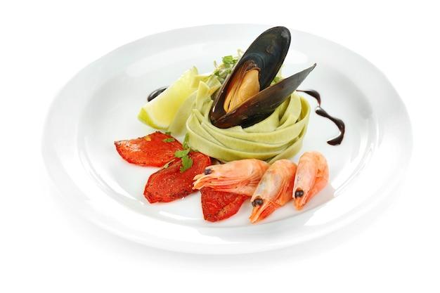 Smaczny makaron z krewetkami, małżami i pomidorami na białym tle