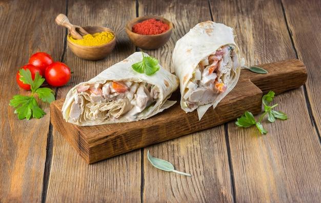 Smaczny meksykański burrito z warzywami, pikantną salsą i limonką