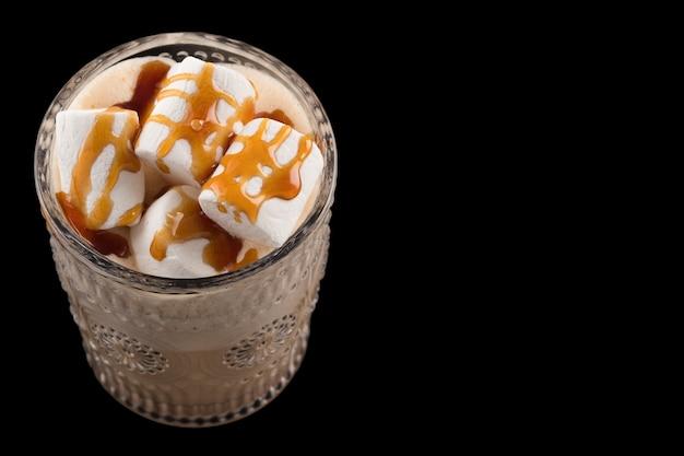 Smaczny napój czekoladowy z pianką i sosem karmelowym na czarnym tle. miejsce na tekst