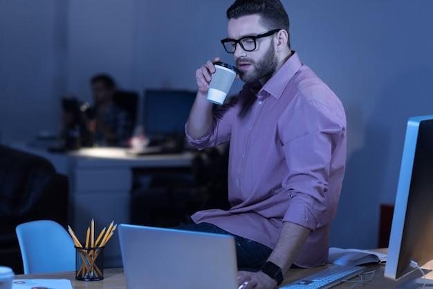 Smaczny napój. ładny przystojny atrakcyjny mężczyzna trzyma filiżankę z kawą i biorąc łyk podczas pracy na laptopie