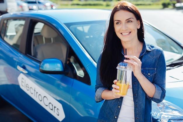 Smaczny napój. wesoła ładna dobrze wyglądająca kobieta stojąca przed swoim samochodem i uśmiechnięta, trzymając sok pomarańczowy