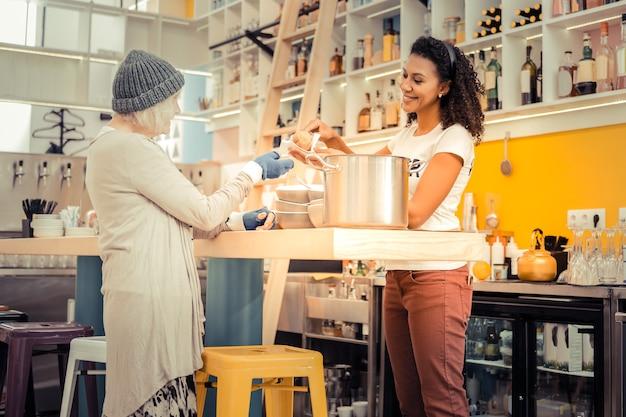 Smaczny obiad. pozytywna kobieta w wieku uśmiechnięta biorąc świeżą bułkę
