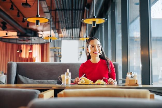 Smaczny obiad. rozpromieniona kobieta z czerwonymi ustami czuje ulgę podczas jedzenia smacznego lunchu w restauracji