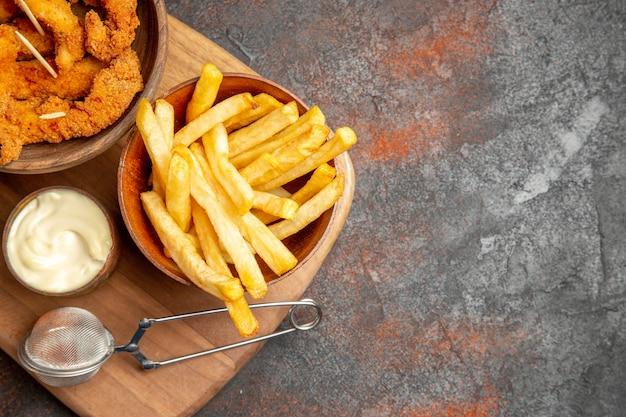 Smaczny obiad z chrupiącym smażonym kurczakiem i ziemniakami z majonezem i ketchupem