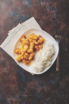 Smaczny obiad z kurczakiem w sosie curry z mlekiem kokosowym z ryżem w białym naczyniu, widok z góry. styl azjatycki.