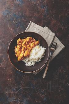 Smaczny obiad z kurczakiem w sosie curry z mlekiem kokosowym z ryżem w ciemnym naczyniu, widok z góry. styl azjatycki.
