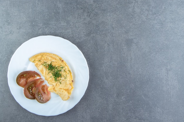 Smaczny omlet i plastry pomidora na białym talerzu