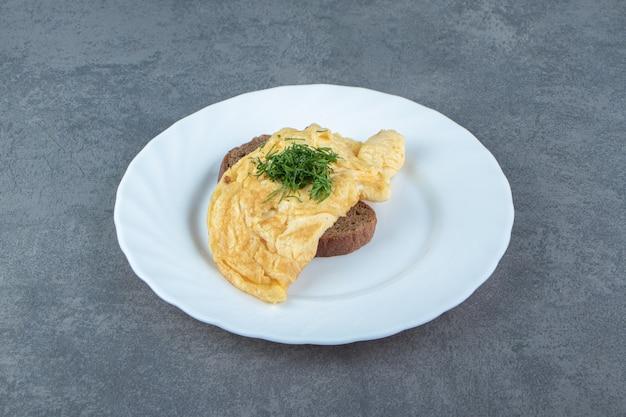 Smaczny omlet z chlebem na białym talerzu.