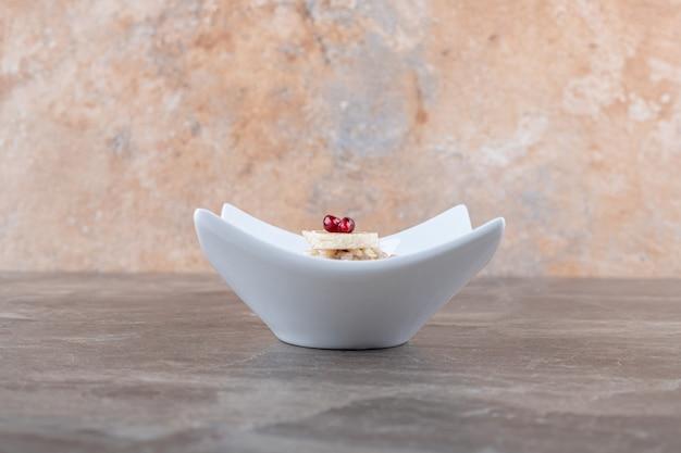 Smaczny owoc granatu na połamanym cieście ryżowym, na marmurowej powierzchni