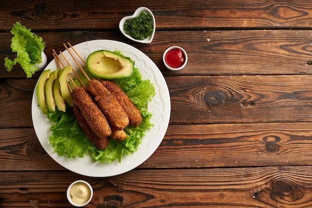 Smaczny pies kukurydziany z sosem i sałatką na białym talerzu na drewnianym stole