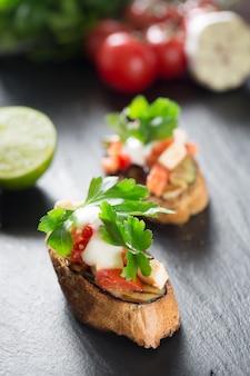 Smaczny pikantny pomidorowy włoski bruschetta, na plasterkach tostowej bagietki przyozdobionej natką pietruszki