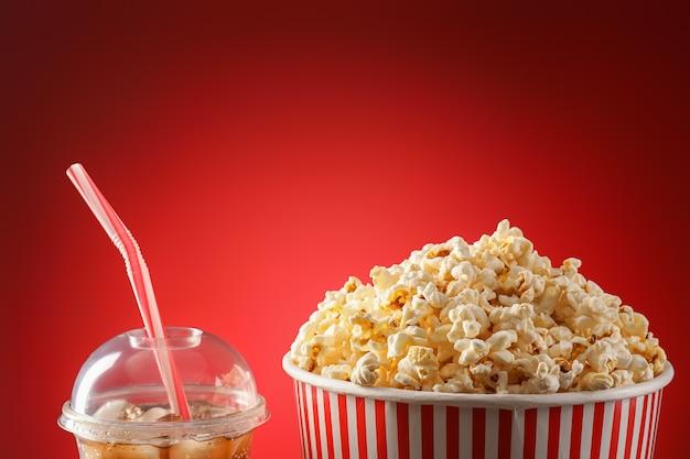 Smaczny popcorn i cola na kolorowym tle