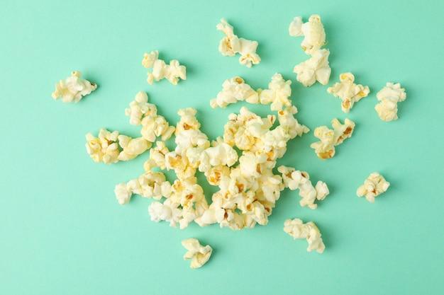 Smaczny popcorn na miętowym tle. jedzenie do oglądania kina
