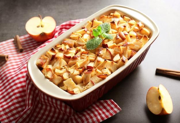 Smaczny pudding chlebowy z jabłkami w naczyniu do pieczenia na stole