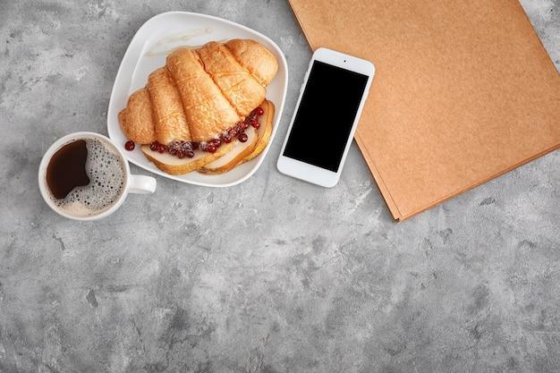 Smaczny rogalik z filiżanką kawy i telefonem komórkowym na stole