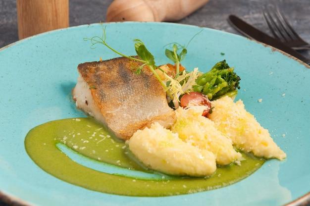 Smaczny sandacz z puree ziemniaczanym na niebieskim talerzu
