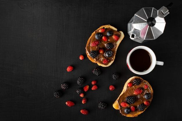 Smaczny słodki tost ze świeżymi jagodami i kawą na śniadanie na ciemnym tle.