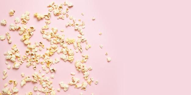 Smaczny słony lub słodki popcorn granicy na różowym tle z miejsca kopiowania. oglądanie filmu, kina, koncepcji.