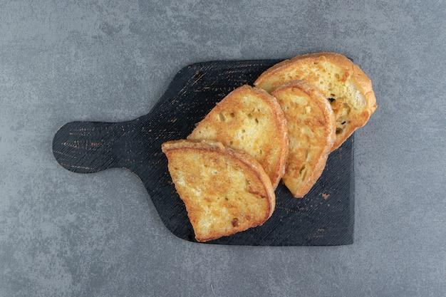 Smaczny smażony chleb z jajkiem na czarnej tablicy.